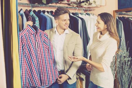 Young loving  cheerful positive couple deciding on new shirt in men's cloths store
