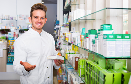 Smiling cheerful male pharmacist wearing white coat standing among shelves in drug store 스톡 콘텐츠