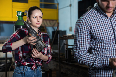 Young woman master is posing with drill in workshop