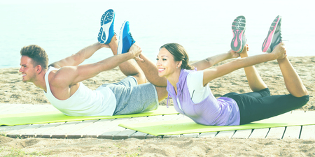 Active guy and girl training on beach by sea in sunny morning