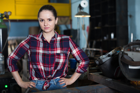 Adult female who is standing on her workplace in workshop