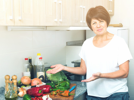portrait of cheerful retiree woman preparing green salad on kitchen at home Stock Photo