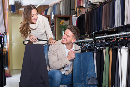 couple choosing new trousers in men's cloths store
