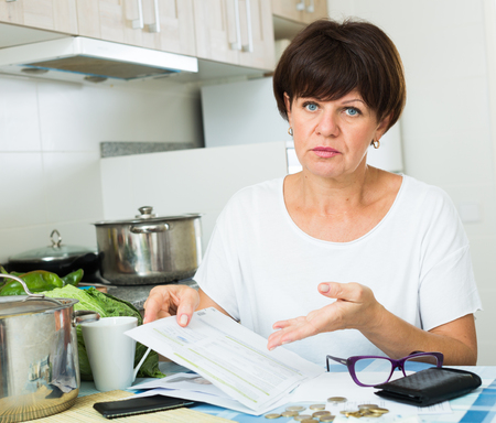 worried senior woman bookkeeping bills and payments at her kitchen