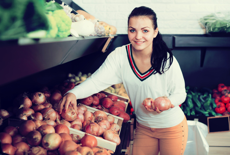Adult smiling woman choosing onions in grocery shop