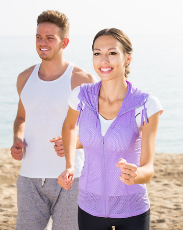 Laughing young couple running on beach by sea at daytime Stock Photo