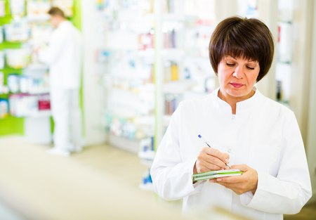 smiling woman pharmacist wearing uniform and working in pharmaceutical shop