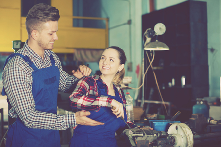 Man who is training young female to repairing drill in workshop Reklamní fotografie