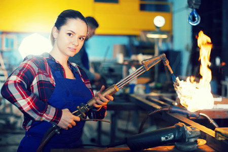 woman worker is standing with burner in workshop. 스톡 콘텐츠