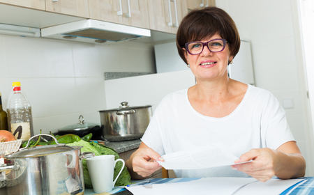 portrait of smiling senior woman bookkeeping bills and payments at her kitchen Фото со стока