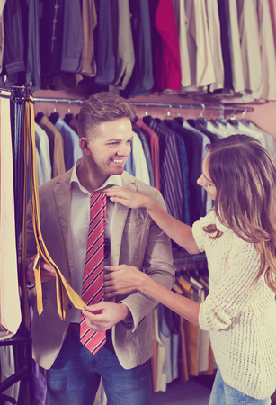 Young smiling couple deciding on tie in men's clothes store