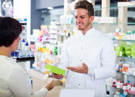 Cheerful man pharmacist wearing coat helping customers in drug store 스톡 콘텐츠