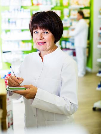 Glad woman pharmacist wearing white coat standing among shelves in drugstore