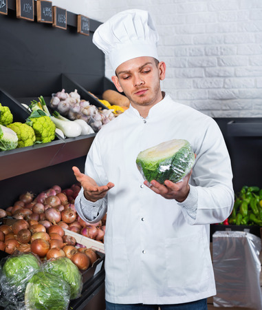 Satisfied pleasant male cook choosing vegetables in grocery shop