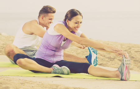 Positive couple doing yoga poses sitting on sunny beach by ocean in morning