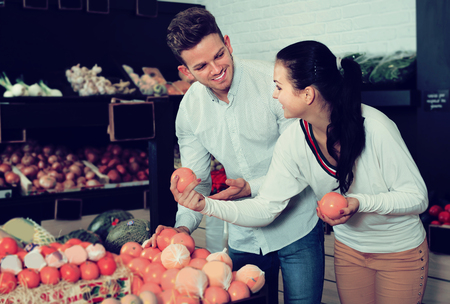 Smiling family examining various fruits in grocery shop