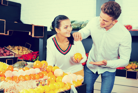 Smiling loving couple deciding on fruits in grocery shop