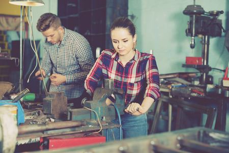 Glad cheerful  smiling girl worker is standing near vise equipment in workshop.