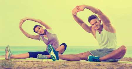 Young glad cheerful couple training yoga poses sitting on beach on sunny morning Stock Photo