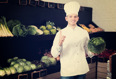 Happy young man cook deciding on best vegetables in grocery shop
