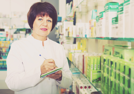 Glad woman druggist wearing white coat standing among shelves in pharmacy 스톡 콘텐츠