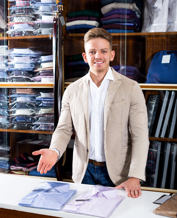 Happy young man seller displaying diverse shirts in men's cloths store Stock Photo