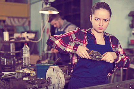 Young woman master is standing with adjustable wrench in workshop. 스톡 콘텐츠