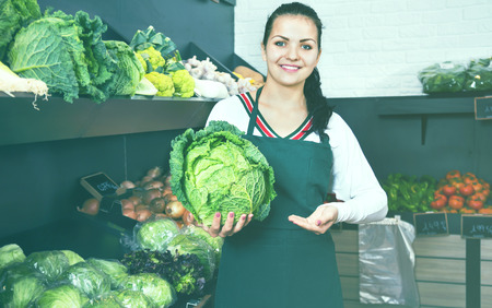Young cheerful smiling woman choosing cabbage in grocery shop