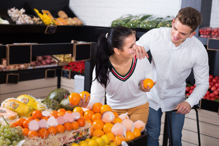 Cheerful couple examining various fruits in grocery shop Stock Photo