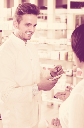 Friendly smiling man pharmacist wearing white coat helping customers in drug store Фото со стока