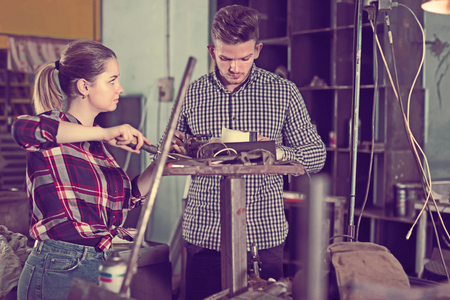 Nice man who is training female to repairing drill in workshop