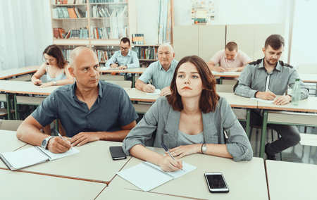 Men and women take a written exam in the classroom