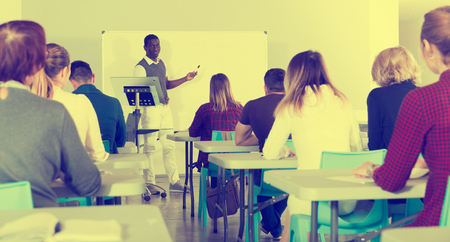 Smiling African American teacher giving presentation for students in lecture hall