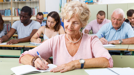Mature woman take a written exam in the classroom