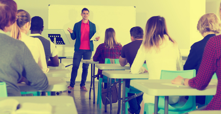 Smiling male teacher giving presentation for students in lecture hall
