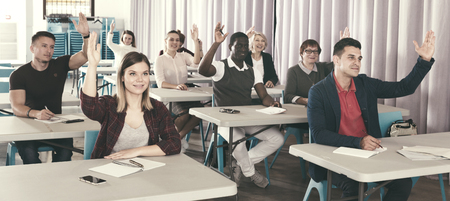 Group of adult people studying together in classroom, raising hands to answer