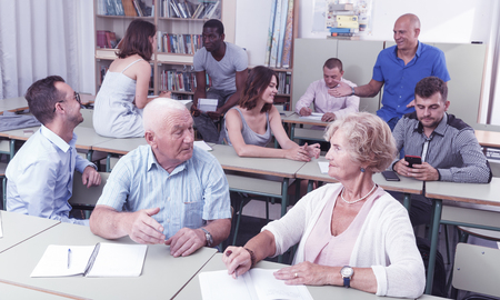 Mature man and woman talking during exam in the classroom Фото со стока