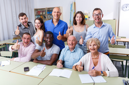Portrait of group students different ages in modern classroom