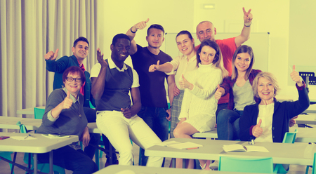 Portrait of happy successful multinational group of adult students in classroom