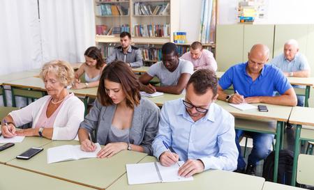 Estudiantes contentos de tareas de escucha de edades mixtas para el examen en el aula