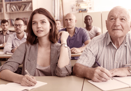 Mature man and girl listening task for exam in the classroom Фото со стока