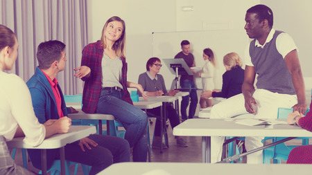 Friendly multinational group of students talking in classroom having break between lessons