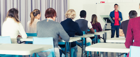 Concentrated adult students of different nationalities with teacher studying in classroom Zdjęcie Seryjne