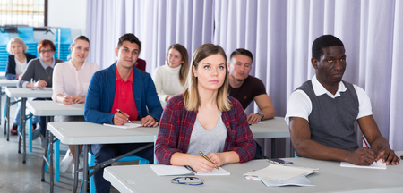 Multinational group of adult students listening teacher in classroom Фото со стока