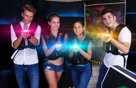 Group portrait of friends girls and guys with guns in their hands in dark laser tag room