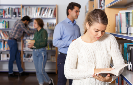 Adult attractive girl reading book while standing near bookshelves in public library Фото со стока