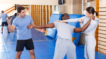 Junges Mädchen, das zu zweit mit einem Afroamerikaner arbeitet, der neue Selbstverteidigungsbewegungen mit männlichem Trainer beherrscht Standard-Bild
