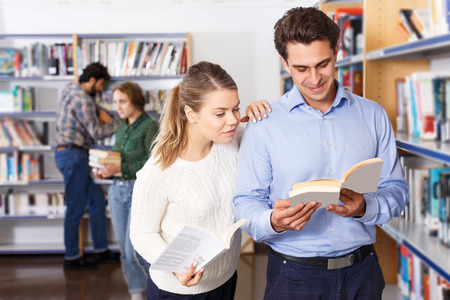 students studying in library, reading and discussing books while standing near bookshelves Фото со стока