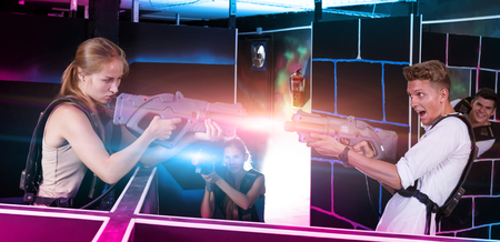 Two exciting players guy and female standing opposite each other with laser guns in dark laser tag room