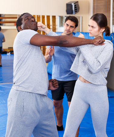 Young girl working in pair with African American man mastering new self defence moves with male coach Reklamní fotografie